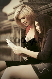 Two young fashion female students reading a notebook