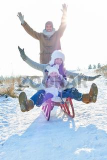 Begeisterte Familie beim Schlitten fahren