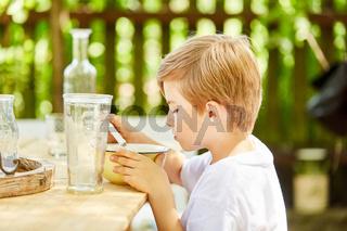 Kleiner Junge isst Müsli zum Frühstück