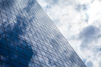 Blue office building with clouds reflection