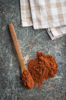 Dark cocoa powder in wooden scoop.