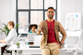 smiling indian man showing thumbs up at office