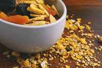 Bowl with different dried fruits on wooden background