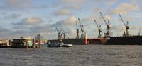 Harbour cranes in Hamburg. Boat on the Elbe.