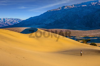 Woman in straw hat  photographing sand waves