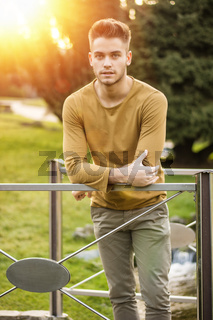 Handsome young man standing in city park