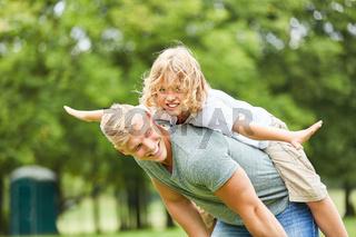 Junge balanciert auf dem Rücken seines Vaters