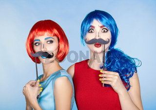 Females in red and blue wigs on blue background. Girls with false moustashes in hands