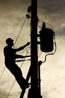Worker silhouette at a power line post