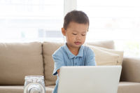 Asian boy using computer laptop.