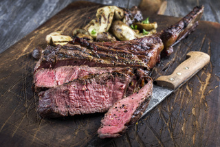 Barbecue Tomahawk Steak with Mushrooms on Cutting Board