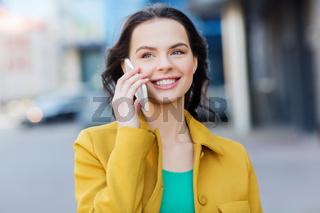 smiling young woman or girl calling on smartphone