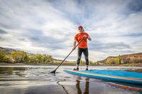 stand up paddling on mountain lake