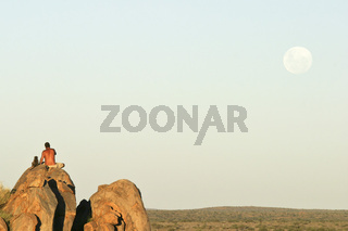 Namibianischer Mann und junger zahmer Steppenpavian, Pavian (Papio cynocephalus) sitzen auf einem Felsen und beobachten den Mondaufgang, Namibia, Afrika, Man with tame Yellow Baboon watches moonrise, Africa