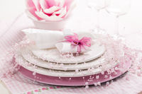 Place setting in pink tone with small present for the guests