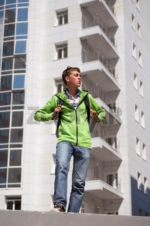 Teen boy with backpack walking on city street
