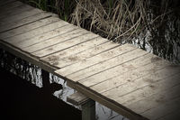 abstract view of a wooden footbridge on small pond