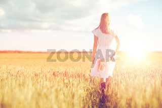 young woman with cereal spikelets walking on field