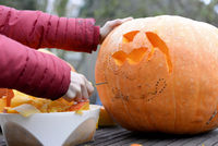 Mädchen bastelt Halloween Kürbis
