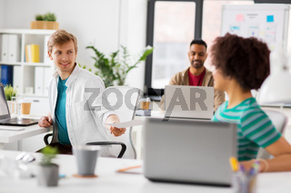happy creative workers with laptops at office