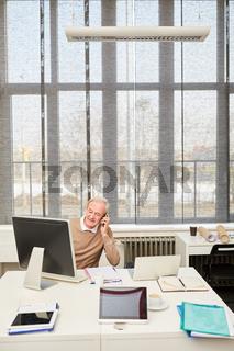 Senior arbeitet am PC und telefoniert