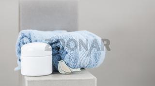 Eine offene Cremedose, daneben Handtücher