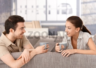 Happy couple sitting on sofa drinking tea smiling