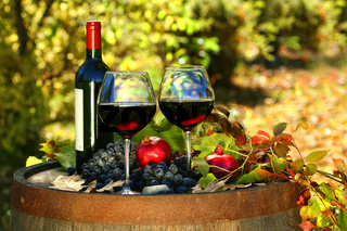 Glasses of red wine on old barrel