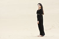 Young brunette standing on sand