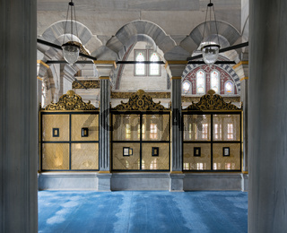 Three gold painted decorated Interleaved wooden windows (Mashrabiya) framed by three marble arches, marble wall and blue carpet, Nuruosmaniye Mosque, Istanbul, Turkey