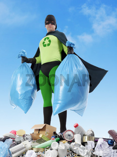 Eco superhero holding two plastic bags full of domestic trash standing on garbage heap