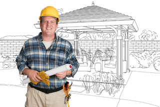 Male Contractor With House Plans Wearing Hard Hat In Front of Custom Pergola Patio Covering Drawing