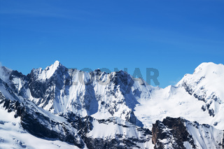 Winter snowy mountains and beautiful blue sky in cold sun day