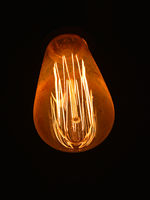 Modern design electric light bulb over black