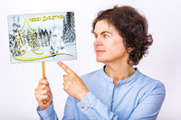 Woman holds sign with Christmas greetings