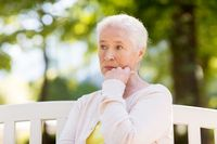 sad senior woman sitting on bench at summer park