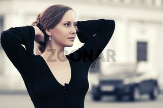 Happy fashion beautiful woman in black blouse walking in city street