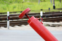 Railway crossing, anti-RAM devices. Red crossing fence device that automatically lifts plates on the road, prohibiting the passage of cars when the train approaches