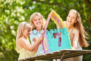 Mutter und Kinder haben Spaß am Hausbau Puzzle