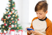 close up of boy with smartphone at christmas
