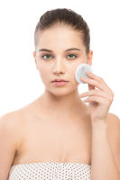 Young woman cares for face skin. Cleaning perfect fresh skin using cotton pad. Isolated.