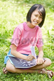 Asiatisches Mädchen malt mit Kreide
