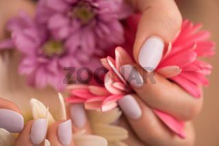 woman hands with manicure holding flower