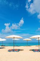 Idyllic beach relaxing concept with white parasols on sand