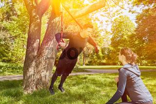 Schlingentraining mit Personal Trainer im Park