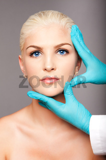Cosmetic plastic surgeon touching aesthetics face