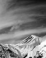 Black and white winter snowy mountains in sun windy day