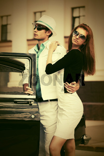 Happy young fashion couple in love next to vintage car