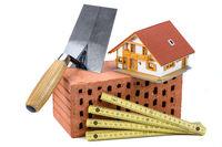 Hausbau mit Ziegelstein und Werkzeug