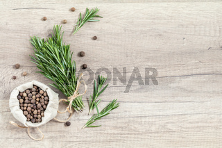 Rosemary and  fragrant pepper on light wooden surface